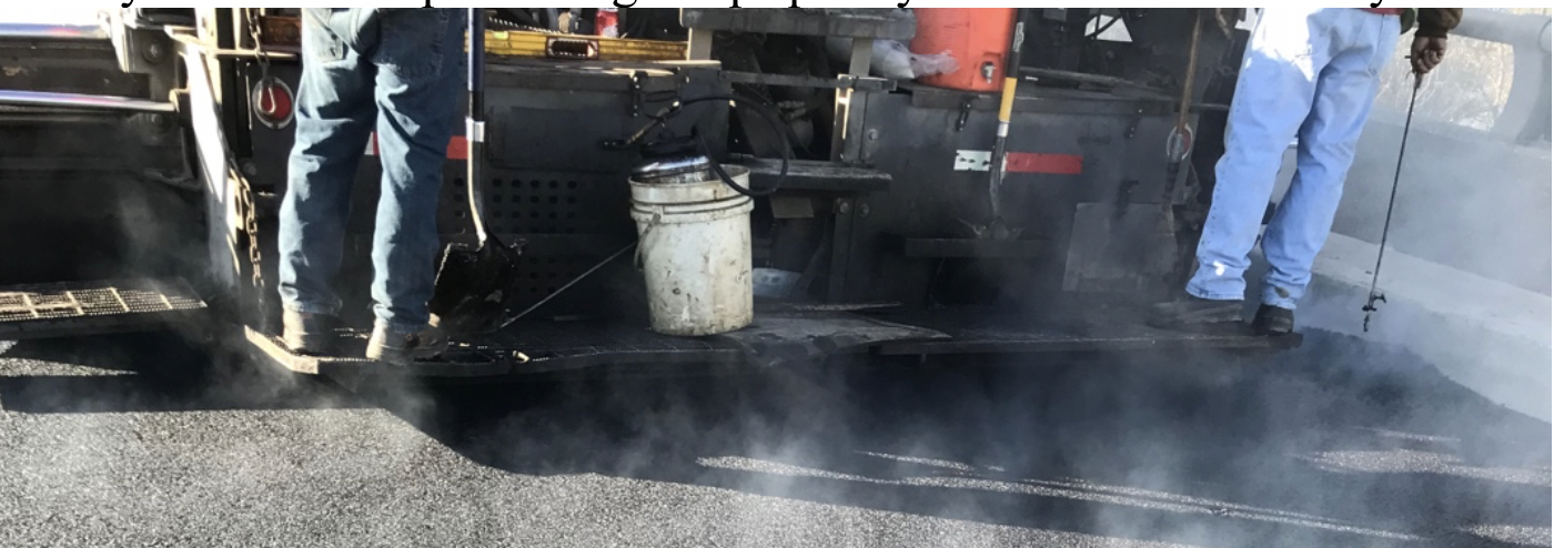 Operator at the right side of the photo is using a dipstick to measure asphalt mat thickness