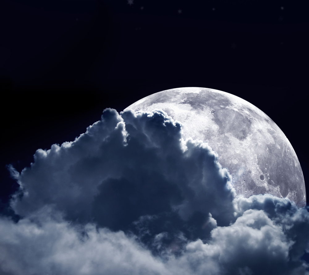 Beautiful shot of a full moon behind some clouds in a dark blue sky